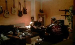 Die spielen doch nur: Pierre Fischer (mitte) und Mario Müller (mit Scharzer Sonne auf dem Rücken) spielen zusammen Gitarre zwischen deutschen Weltkriegswaffen und NS-Devolitäten in Müllers Wohnung. (Quelle: facebook)