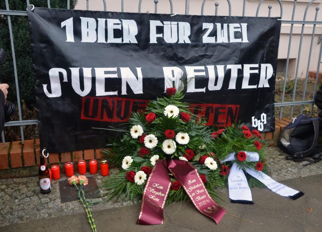 An der Gedenktafel für Sven Beuter legten Aktivist_innen und Freunde Blumen, Kerzen und als besonderes Andenken mehrere Flaschen Bier nieder. Foto: Ney Sommerfeld.