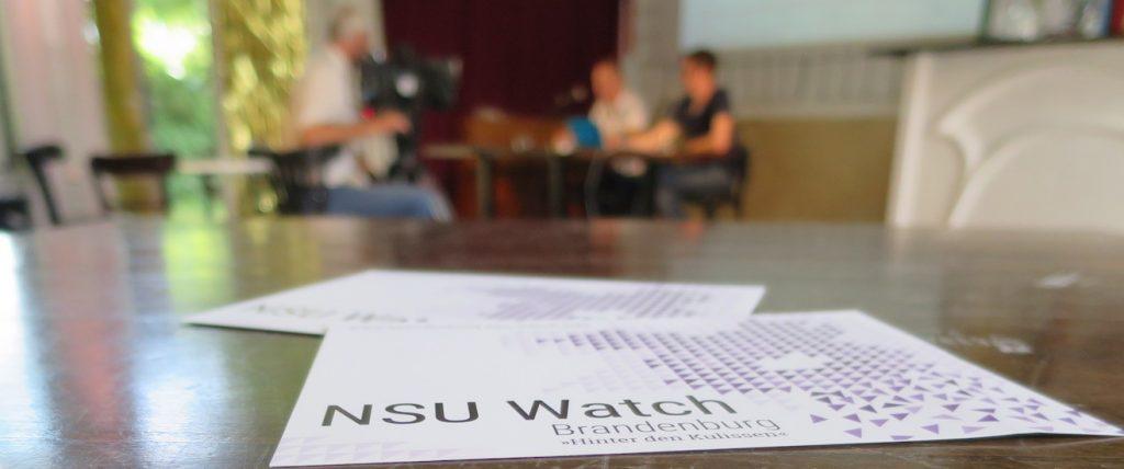 Foto zeigt einen Flyer von NSU Watch Brandenburg im Vordergrund und Personen im Hintergrund