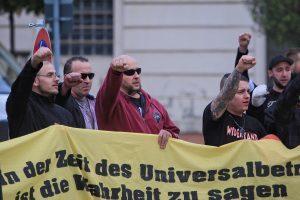 """Tony Schmidt (ganz rechts im Hintergrund) hebt zum Ende der Kundgebung am 25. Oktober 2014 in Brandenburg/Havel die Faust und fordert zusammen mit den restlichen Teilnehmer_innen einen """"Nationalen Sozialismus"""". Vorne am Transparent (mit rotem Pullover) der Neonazi und Totschläger Sascha Lücke."""